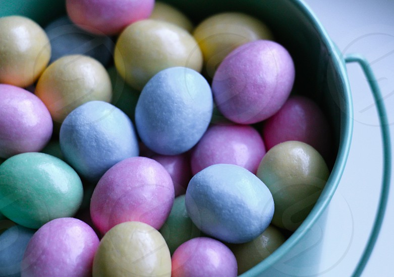 close up photo of blue pink and yellow candies in a green bucket photo