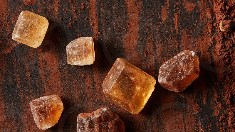caramel pieces with cocoa powder on a dark background photo