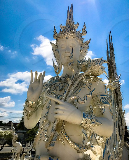 Outdoor day vertical portrait colour Wat Rong Khun The White Temple Chiang Rai Thailand Thai Kingdom of Thailand travel tourism tourist wanderlust summer summertime temple Buddhist Buddhism spiritual pure holy dragon monster carved ornate elaborate art modern sculpture sculpted east eastern hands silver mirror mosaic magical mythical blue sky contrast goddess Buddha photo