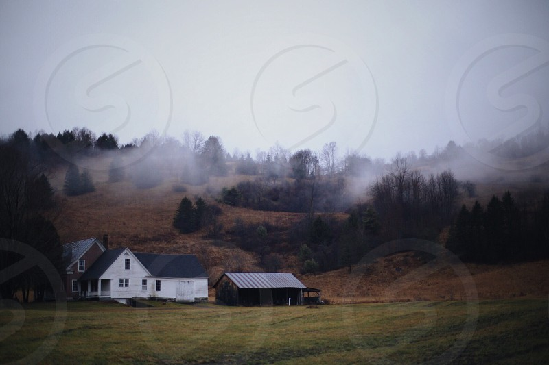 white farmhouse with barns and foggy trees on hills in the distnce photo