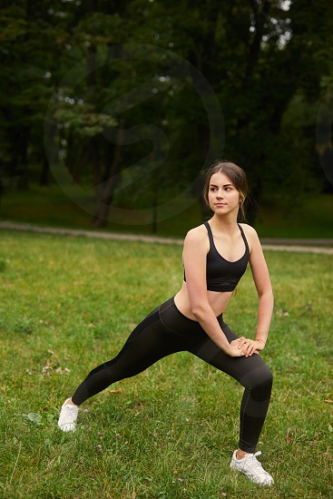 Sporty girl squats on the grass photo