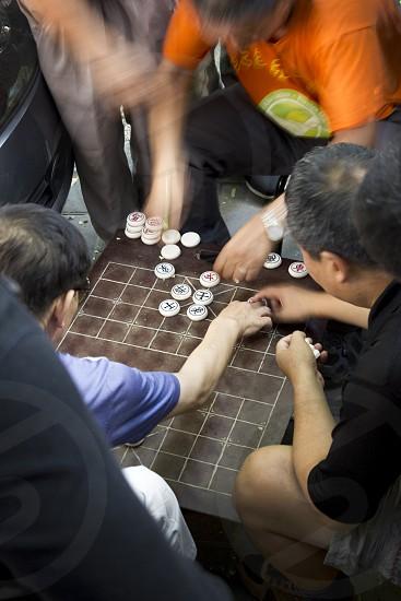 china men playing a game street photo