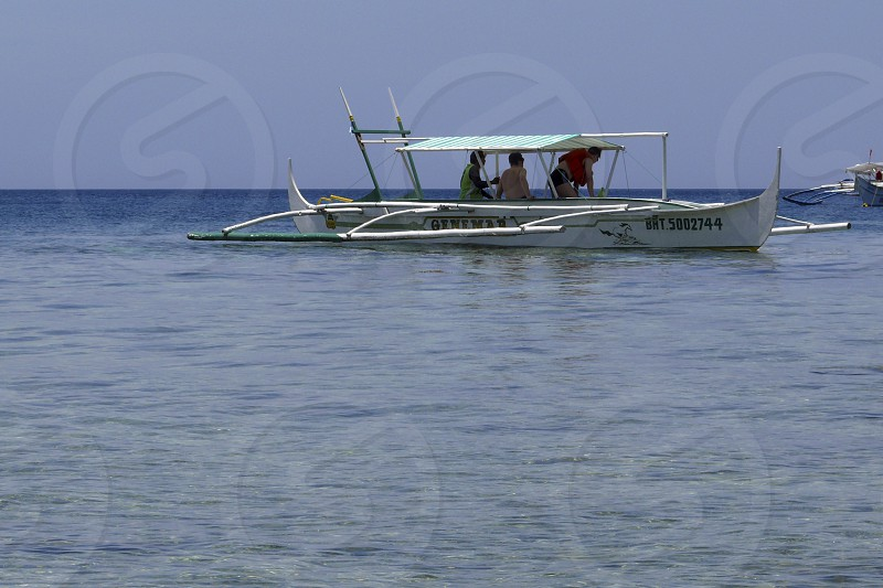 3 people on the white motorboat photo