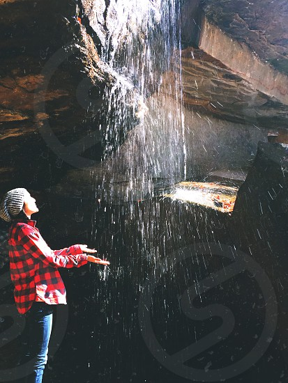 woman in red and black checked sports shirt catching waterfall during daytime photo