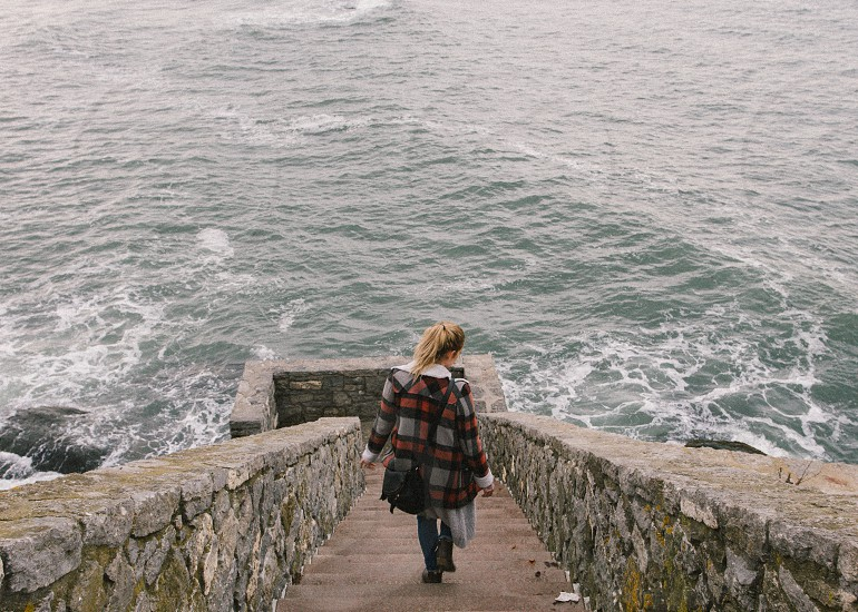 woman with red and gray plaid coat taking a step near body of water during daytime photo