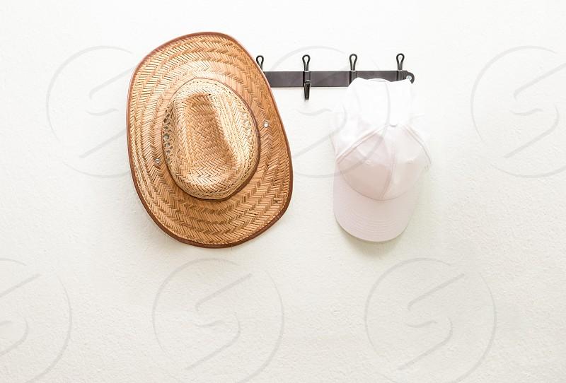 brown cowboy hat hanging on wall beside white mesh cap photo