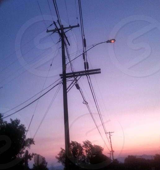 Electrical Wires Utility Poles and a Sensory Activated Street Light at dusk in a rual town. photo