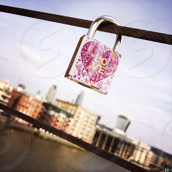 A love lock padlocked to Millennium Bridge in London England. After the padlock has been locked the key is thrown away to symbolise in breakable love.  photo