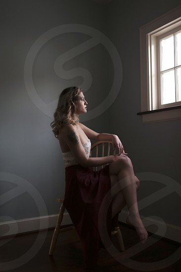 Woman sitting alone while starring out the window deep in thought. photo