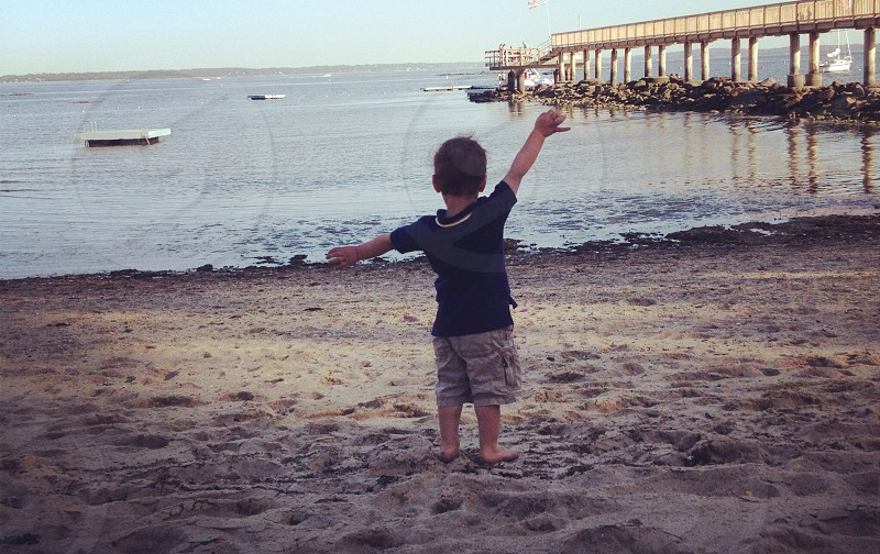 Boy toddler expresses his happiness on the beach. photo