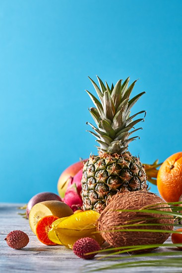 Creative layout made of fruits pineapple orange lime pitaya carambola coconut mango kumquat with exotic palm leaf on a gray wooden table on a blue background copy space photo