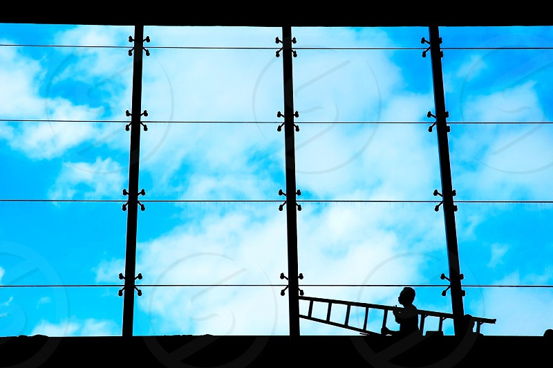 Silhouetted image of a man carrying ladder against large interior windows and blue sky. photo
