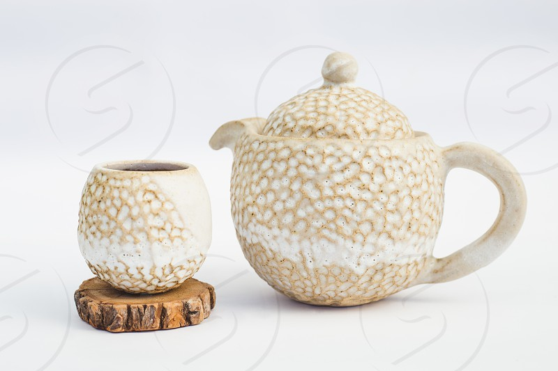 beige teapot and ceramic stoneware cup with white background photo