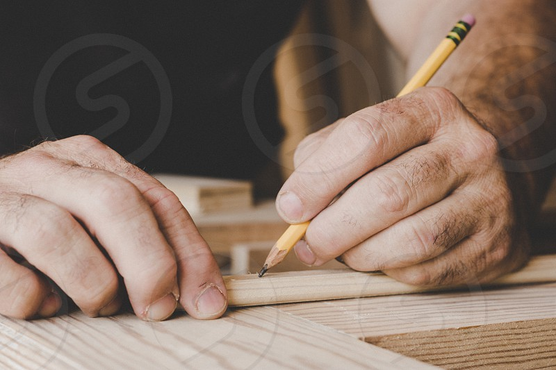A man uses a pencil to mark a piece of trim he is going to cut as he works on a door for his home. photo