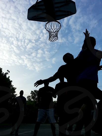Staying Healthy by playing Basketball basketball sports workout fitness recreational sports men playing athletes athletics silhouettes males basketball net jumping mid air mid-air team sports photo