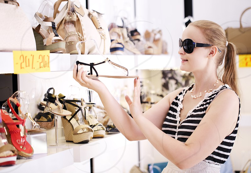 Young woman in sunglasses choosing summer shoes in the shop photo