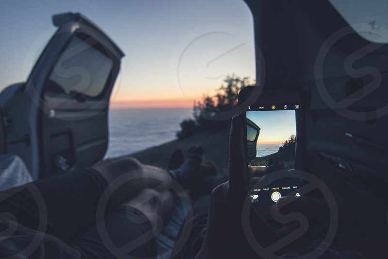 human lying in car while holding iphone and taking photo of sea during sunset photo