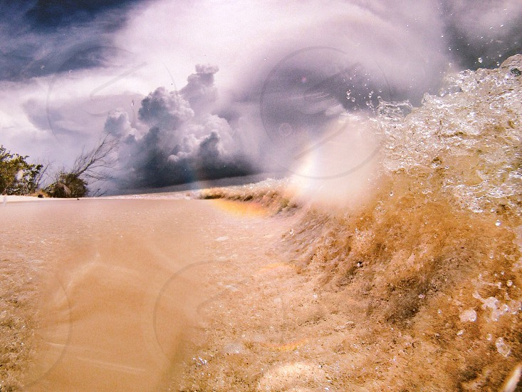 wave over brown beach sand photo