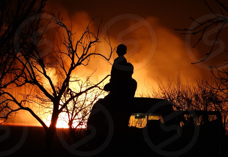 Fire & Flame - Silhouette of father and son watching a blazing fire photo