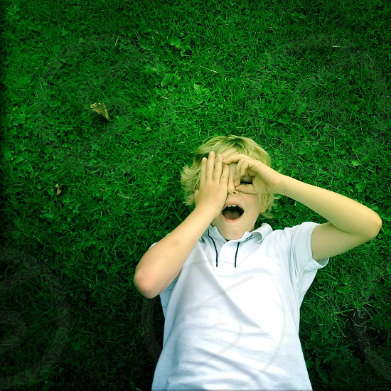 boy in white polo shirt lying on green grass photo