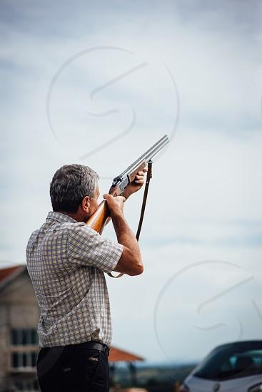 Older man shooting shotgun in the sky photo