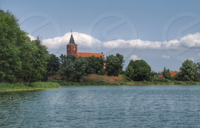 landscape church lake tree sky Poland photo