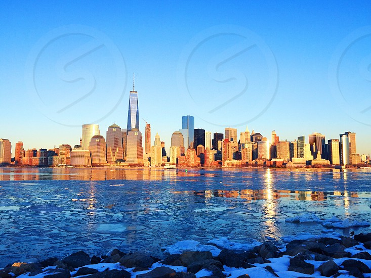 landscape photography blue body of water overlooking high risen building city under blue skies photo