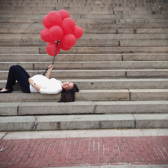 woman in white quarter-sleeved shirt holding bunch of red inflated balloons lying on gray concrete stairs photo