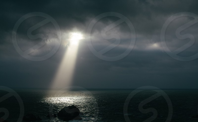 Dramatic ray of sunlight creating a spotlight on the Pacific Ocean. photo