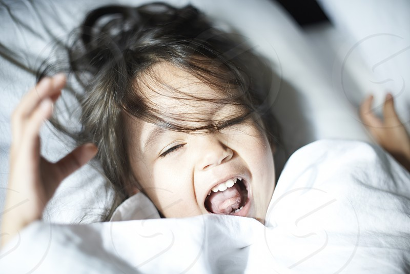 Cute portrait of a young Asian toddler girl looking into camera and happily shouting in bed in bright sunlight photo
