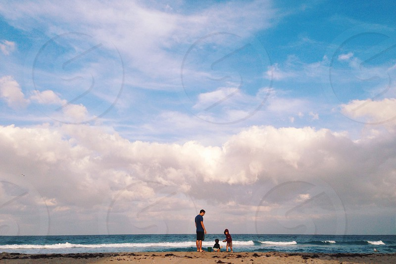 A father and young sons play at the beach photo