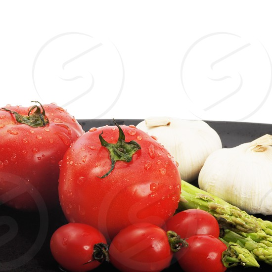 plate of fresh tomatoes ;cherry tomatoes asparagus and garlic typical mediterranean food photo
