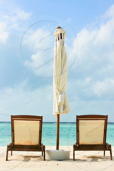 2 brown recliner chairs on beach sand photo
