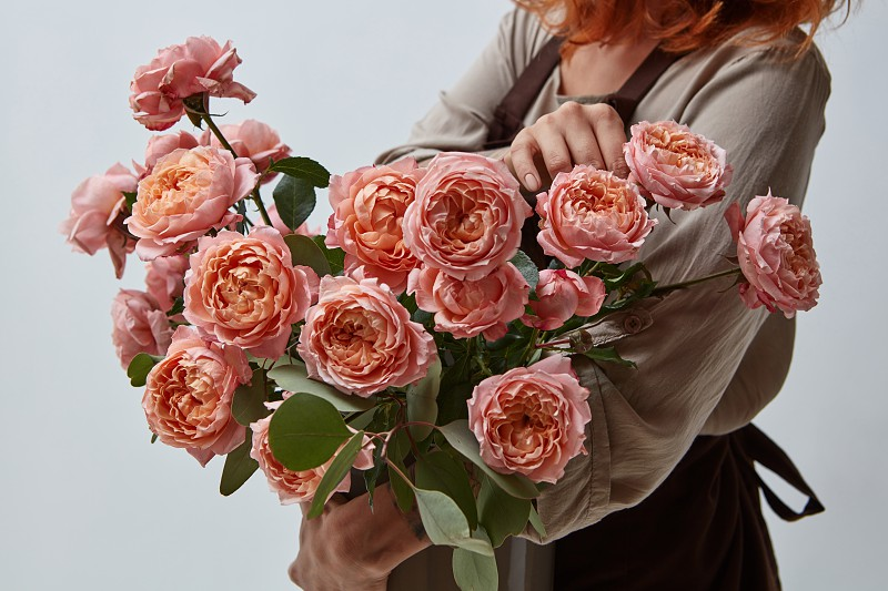 Fragrant pink media roses in a vase. A young girl holding a vase with flowers. Mothers Day. Flowers shop concept photo