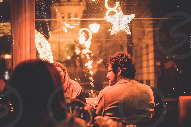Group Of Friends Enjoying Christmas Drinks At Night Out Bar Restaurant photo