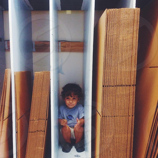 a small boy playing among boxes in a shipping store photo