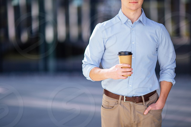 Businessman holding his coffee or tea drink on blur background photo