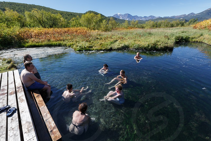 NALYCHEVO NATURE PARK KAMCHATKA PENINSULA RUSSIA - SEP 7 2013: Group hot springs in Nalychevo Nature Park - people take a therapeutic (medicinal) baths in pool with natural thermal mineral water having balneological properties. photo