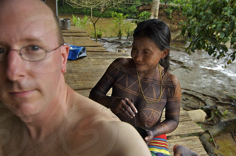 I receive temporary tattooing deep in the Panamanian rainforest from an Embera village woman herself covered in the tree bark mixture used in tattooing. photo