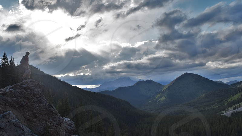 A hiker stands tall over a valley of beautiful mountains with dramatic sky over him  photo