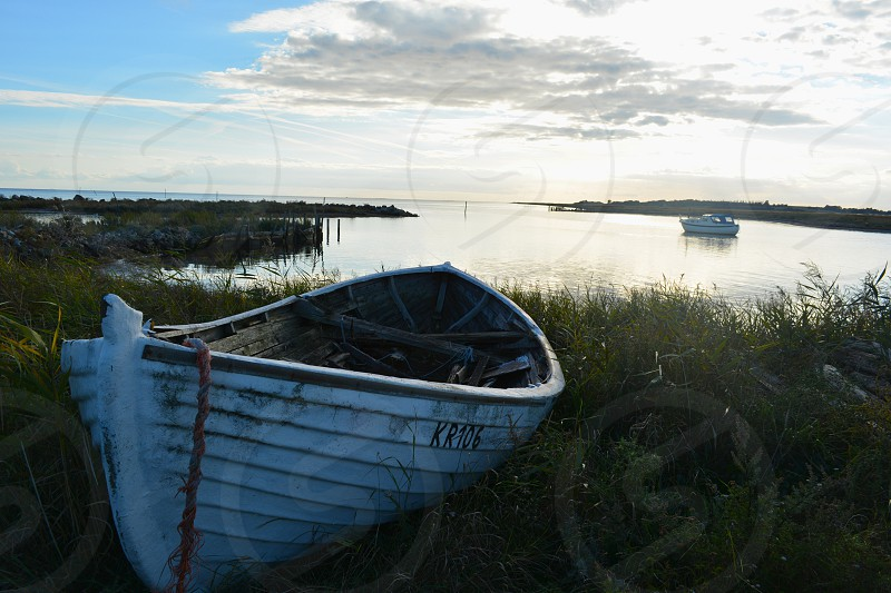 white row boat on the shore photo