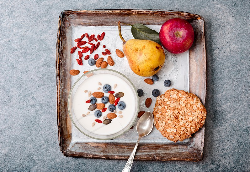 Breakfast on table. Yogurt with added blueberries and roasted almonds. Muesli cookie apples and pears on table. Light and healthy meal. Good quality balanced diet. Flat top-down composition photo