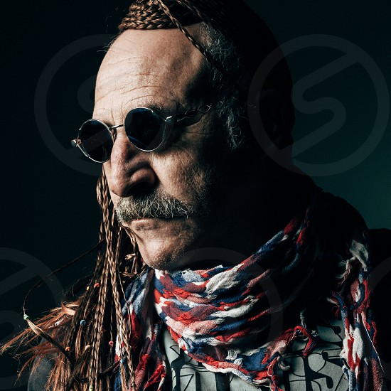 Stylish Middle Aged Man with Braided Hair. Close up Stylish Middle Aged Man with Braided Hair Wearing Sunglasses with Scarf Around his Neck Against Dark Blue Green Background. photo