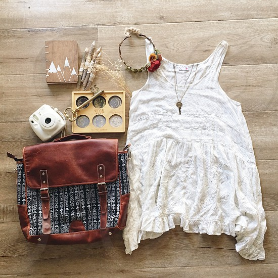 women's white tank top beside brown and black sling bag on brown wooden parquet flooring photo