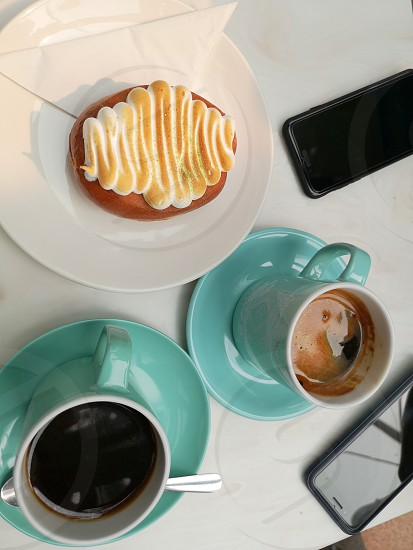 two people catching up over coffee and a doughnut photo