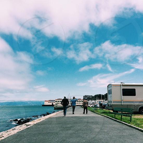 3 men walking near sea shore view photo