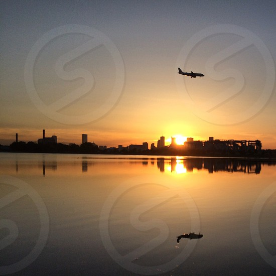 air plane flying over an orange sunset photo