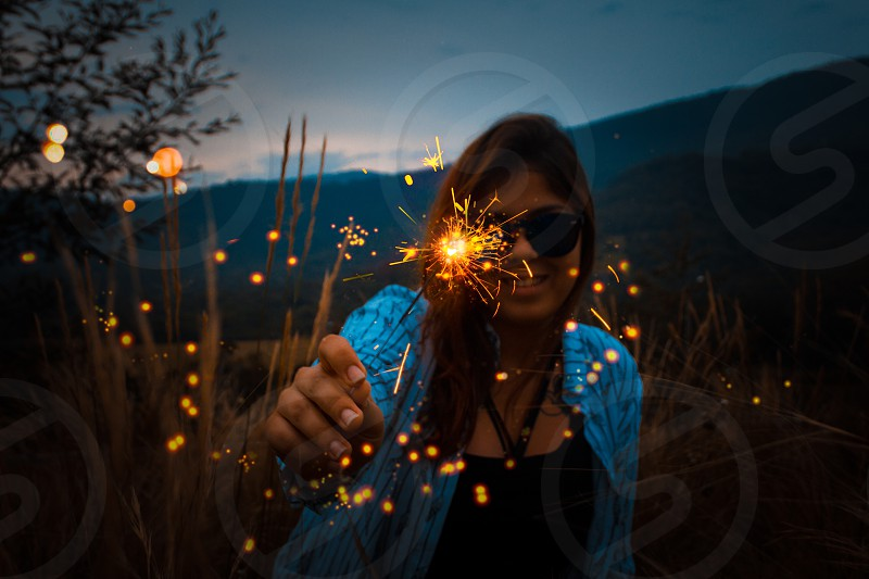 Young girl holding a birthday candle in an open field. Lights with effect bokeh. photo