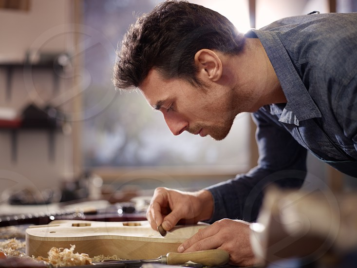 work; instrument; guitar; lutemaker; lute-maker; man; accuracy; adult; 30s; artisan; body; carpentry; carving; concentration; crafts; craftmanship; craftsperson; custom; design; desk; electric; entrepreneur; expertise; focusing; handcrafted; handmade; indoors; italian; job; luthier; manual; music; musical; one; people; person; planing; precision; polishing; product; shop; skill; small business; smoothing; table; tool; waist up; wood; working; workshop photo