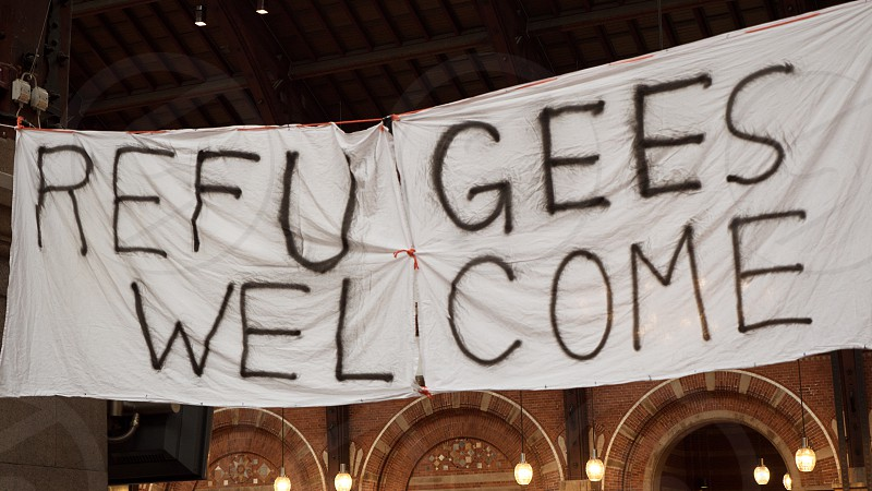 Handmade banner Refugees Welcome is hanged in Copenhagen railroad station by the place where locals bring clothes for refugees. photo